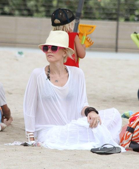 Gwen Stefani usa óculos rosa em praia